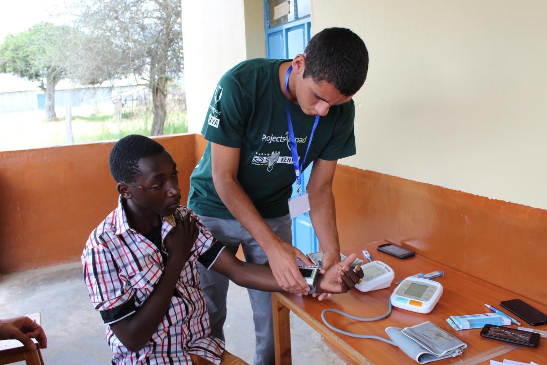 Un adolescente midiendo la presión sanguínea durante su voluntariado médico.